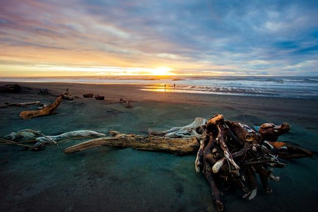 Persone sulla spiaggia di sabbia di hokitika southland nuova zelanda