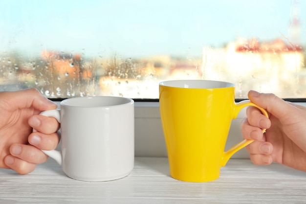 Persone che tengono le tazze contro la finestra