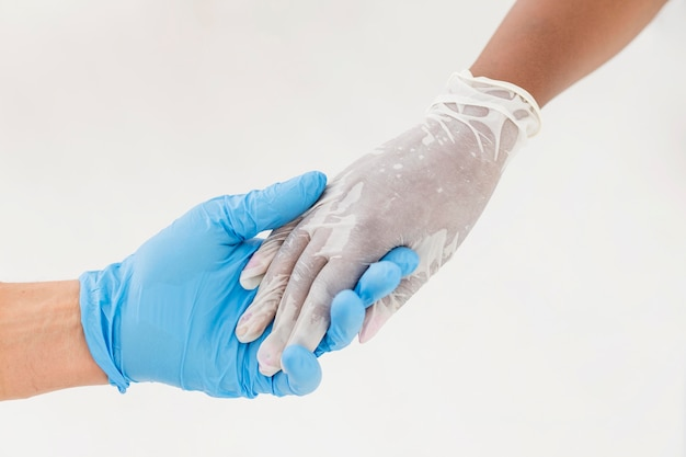 Persone che si tengono per mano mentre indossano guanti medicali