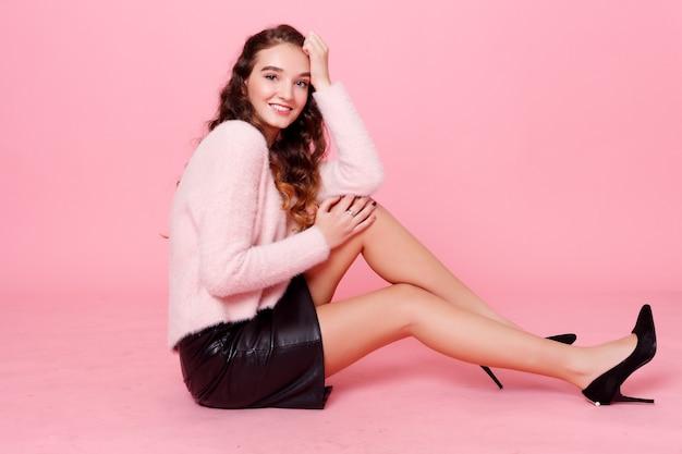 Persone, vacanze, concetto di lusso - bella giovane donna sorridente in una gonna di pelle nera che presenta qualcosa e guarda la macchina fotografica. studio girato sfondo rosa. ritratto di una bella ragazza adolescente