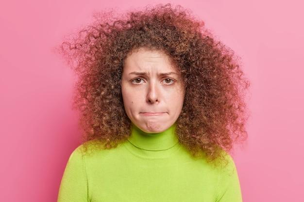 Concetto di reazioni ed emozioni umane di persone. la giovane donna europea dai capelli ricci insoddisfatta e preoccupata vuole piangere preme le labbra vestite con un dolcevita verde casual isolato sul muro rosa.