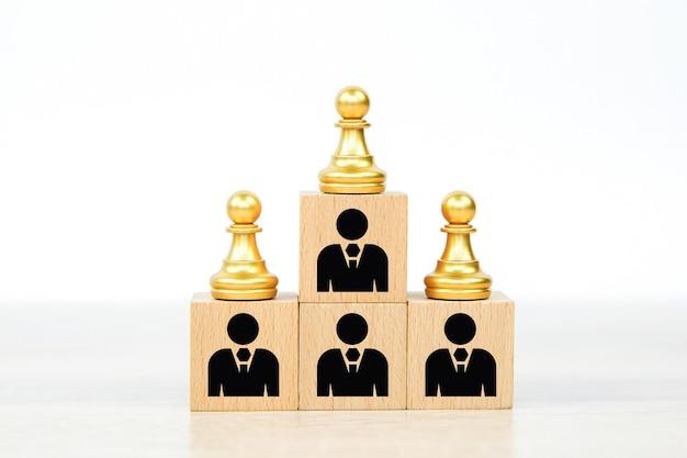 Persone icone e pezzo degli scacchi su blocchi di legno impilati.