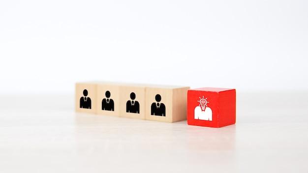 Icone della gente sui blocchetti del giocattolo di legno del cubo impilati.