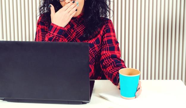 Concetto di persone, lavoro, carriera e superlavoro. triste ufficio occupato donna che lavora al computer portatile in ufficio.