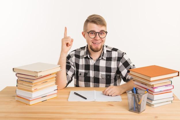 Concetto di persone, conoscenza e istruzione - studente intelligente seduto al tavolo con libri e taccuino.