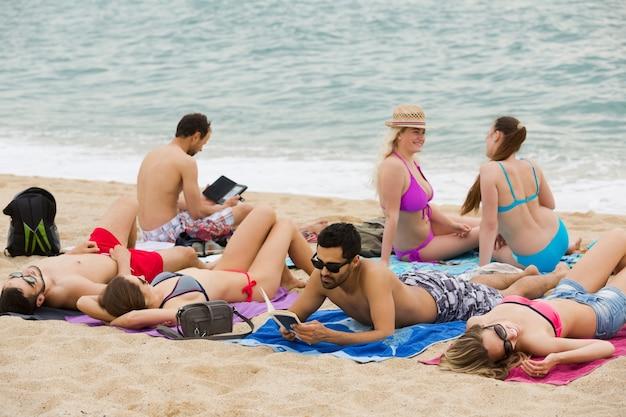 Persone che si distendono sulla sabbia in spiaggia