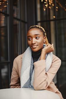 Persone e concetto di tempo libero. primo piano del volto di una bella ragazza africana. donna che mantiene tazza di bevanda calda.