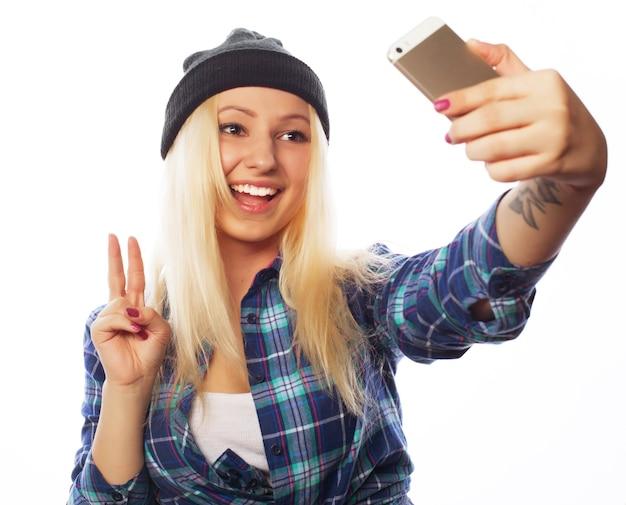 Persone, stile di vita e concetto di tecnologia: bella ragazza adolescente che indossa un cappello, scatta selfie con il suo smartphone - isolato su bianco