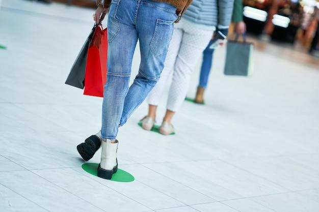 Persone in fila/coda al supermercato/centro commerciale a distanza sociale durante la quarantena/epidemia