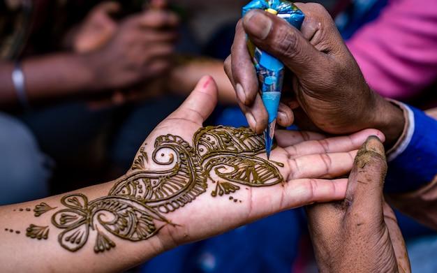 Persone che fanno arte mehndi a portata di mano durante il festival sharwan a kathmandu nepal