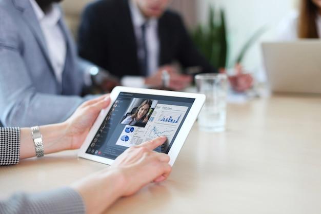 Persone che si incontrano analizzando le statistiche finanziarie in ufficio. gruppo di team aziendali che hanno videoconferenza con il proprio team su tablet digitale, lavoro a distanza a casa.