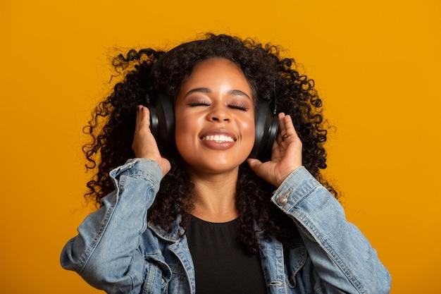 Persone, musica, concetto di emozioni. deliziosa donna spensierata con acconciatura afro balla al ritmo della melodia, chiude gli occhi ascolta la canzone ad alta voce in cuffia. bella donna afro con le sue cuffie