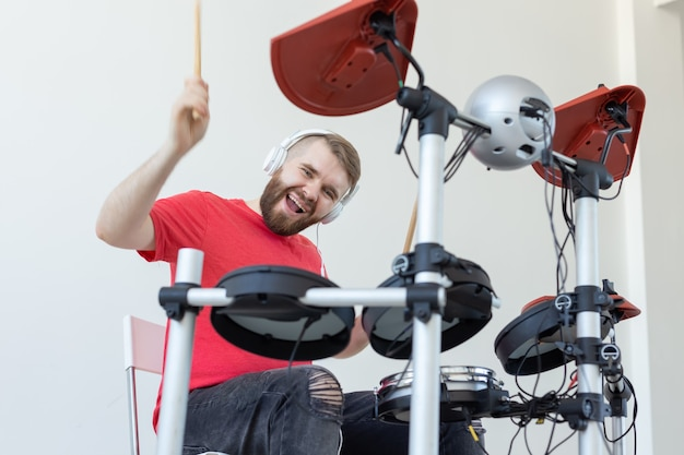 Concetto di persone, musica e hobby - uomo felice che trascorre il suo tempo libero suonando la batteria