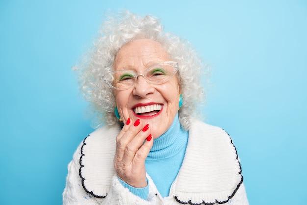 Concetto di emozioni positive di vecchiaia della gente. felice signora dai capelli grigi sorride ampiamente ha denti bianchi e uniformi indossa un trucco luminoso
