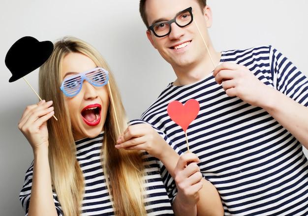 Concetto di persone, feste, amore e tempo libero - bella coppia con occhiali da festa e cappello su bastoncini, su sfondo grigio
