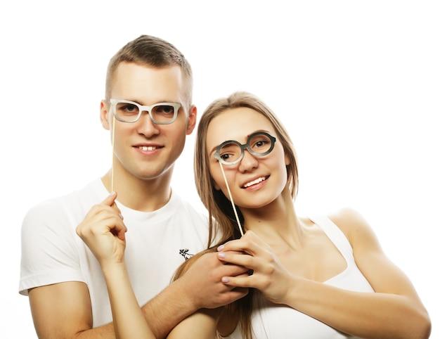 Concetto di persone, feste, amore e tempo libero - coppia adorabile che tiene occhiali da festa e baffi su bastoncini, su sfondo bianco