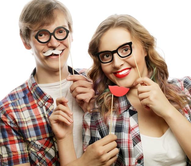 Persone, festa, amore e concetto di svago - coppia adorabile che tiene occhiali da festa e baffi su bastoncini, su sfondo bianco
