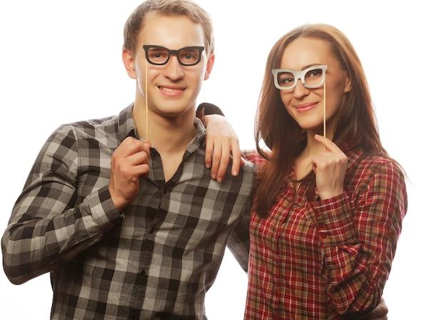 Concetto di persone, festa, amore e tempo libero - coppia adorabile che tiene occhiali da festa e baffi su bastoni,