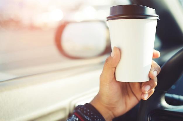 Persone persona che beve caffè tazza di carta di caldo in mano durante la guida in macchina al mattino