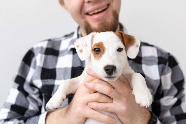 Concetto di persone, animali domestici e animali - chiuda in su del giovane che tiene il cucciolo di jack russell terrier su bianco