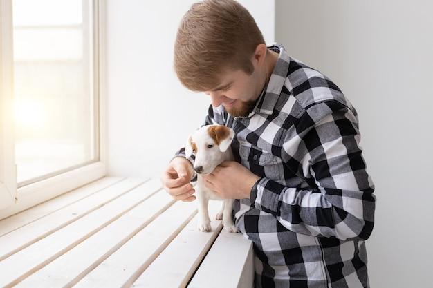 Concetto di persone, animali domestici e animali - giovane che abbraccia il cucciolo di jack russell terrier vicino alla finestra su sfondo bianco.