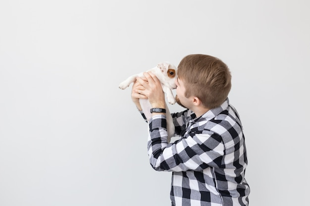 Concetto di persone, animali domestici e animali - giovane che bacia jack russell terrier cucciolo su sfondo bianco con spazio di copia copy