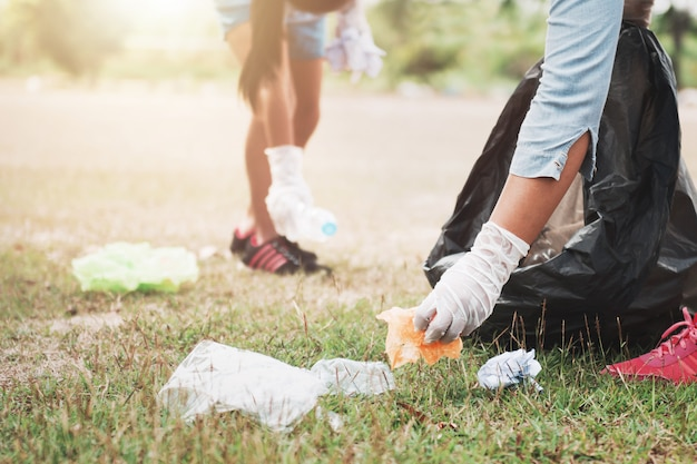 La gente raccoglie la spazzatura e la mette nella busta di plastica nera