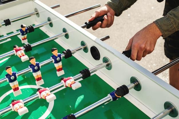 La gente che gioca godendo del tempo libero di ricreazione del gioco di calcio della tabella di calcio-balilla