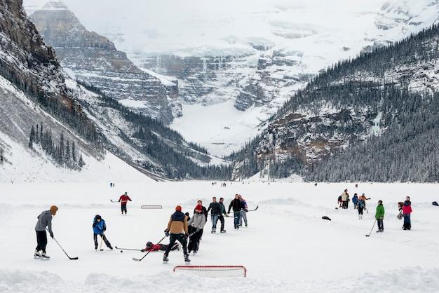 Persone che giocano a hockey su ghiaccio, lake louise, parco nazionale di banff, alberta, canada