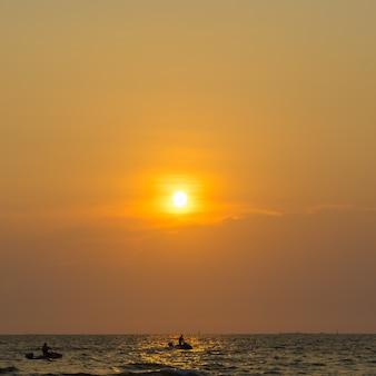 Persone che giocano a jet ski in mare con il tramonto