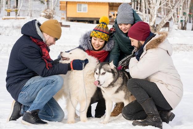 Persone che giocano con i cani in vacanza