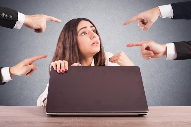 Persone che indicano una donna nascosta dietro un computer
