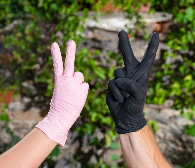 Persone in guanti protettivi che mostrano il segno di vittoria