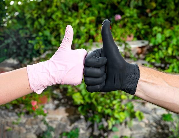 Persone in guanti protettivi che mostrano il segno sì