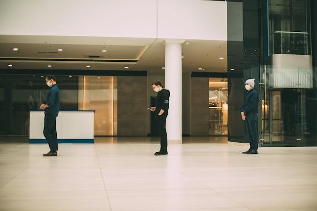 Persone con maschere protettive in fila e a distanza.