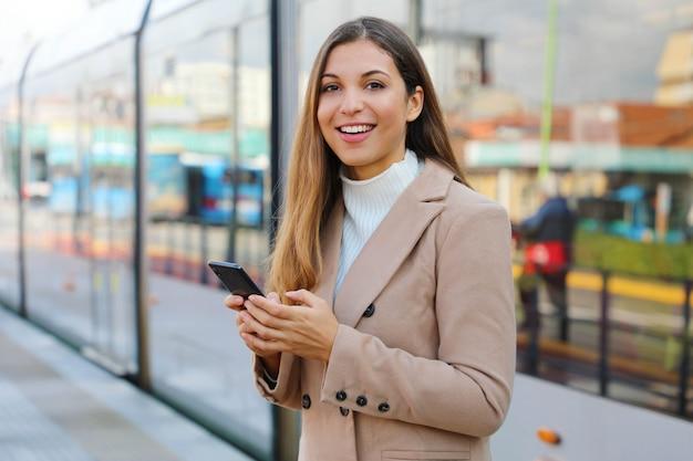 Persone e trasporti pubblici. bella donna felice che tiene cellulare alla fermata del tram.