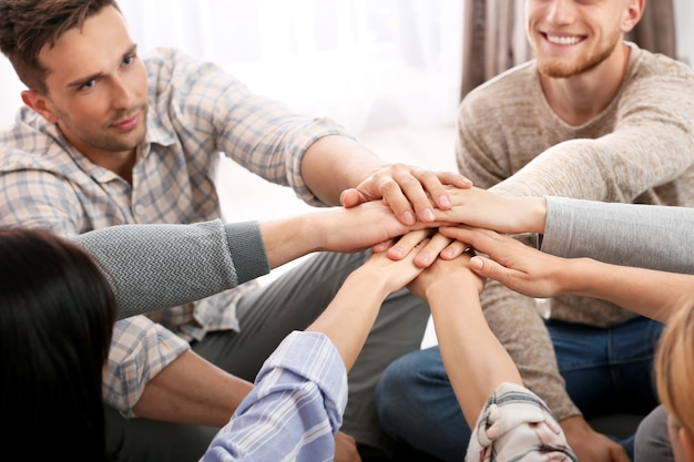 Persone che mettono le mani insieme alla sessione di terapia di gruppo