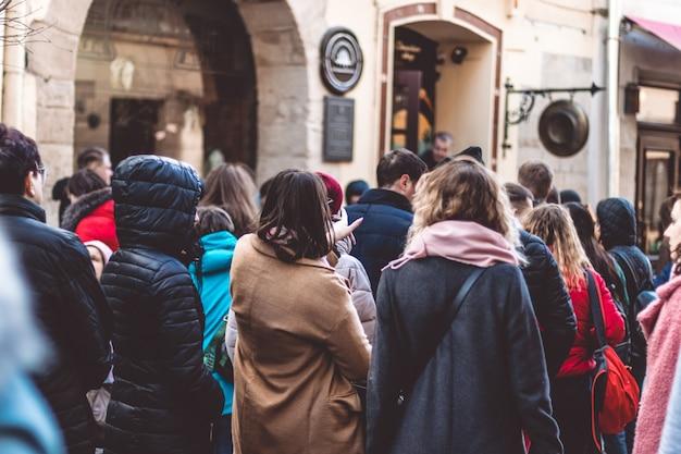Le persone fanno la coda in fila, trascinate in una fila di persone in un ambiente urbano