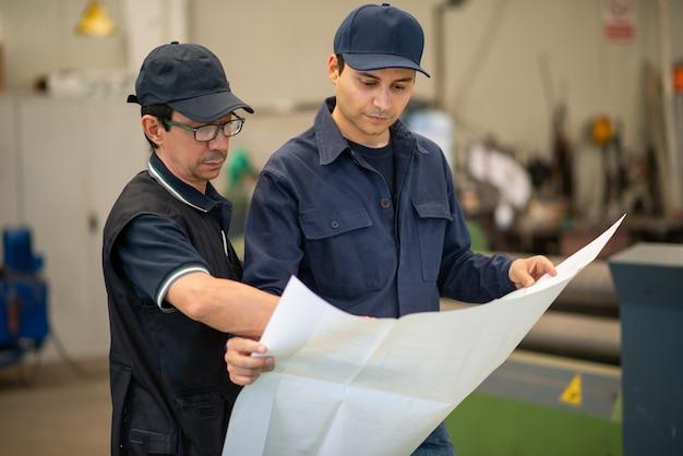 Persone che leggono un disegno in una fabbrica industriale