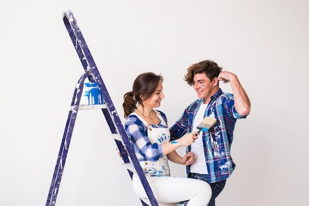 Concetto di persone, ristrutturazione e riparazione - bella coppia si diverte durante la ristrutturazione