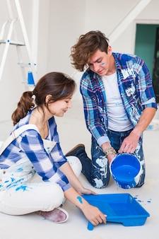 Persone, ristrutturazione e concetto di riparazione - ritratto di coppia felice versare vernice
