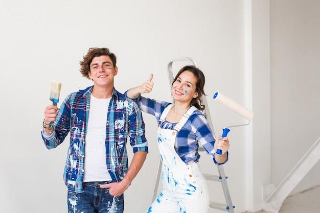 Persone, riparazione e concetto di appartamento - bella giovane coppia che fa lavori di ristrutturazione in appartamento.