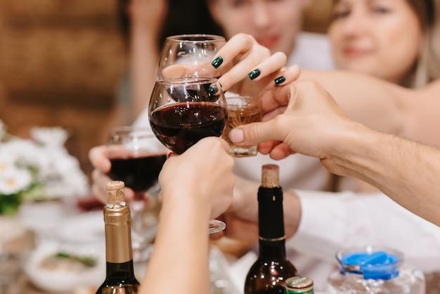 Le mani della gente tintinnano bicchieri con bevande alcoliche in una vacanza in un ristorante