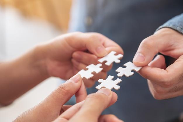 Le mani della gente che tengono e mettono insieme un pezzo di puzzle bianco
