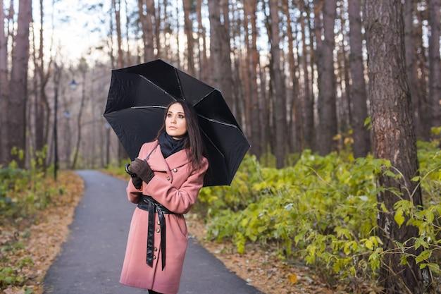 Persone, stagione e concetto di moda - bella giovane donna nel parco in autunno con l'ombrello