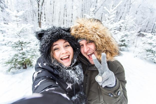 Persone, stagione, amore, tecnologia e concetto di svago - coppia felice che si fa selfie con lo smartphone su sfondo invernale
