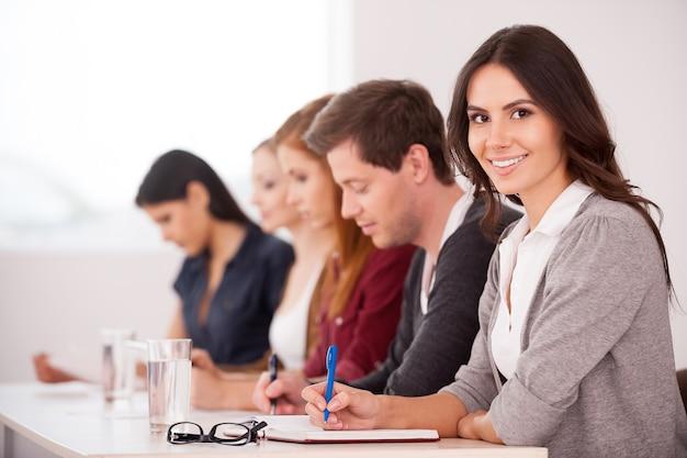 Persone al seminario. attraente giovane donna che sorride alla telecamera mentre è seduta insieme ad altre persone al tavolo