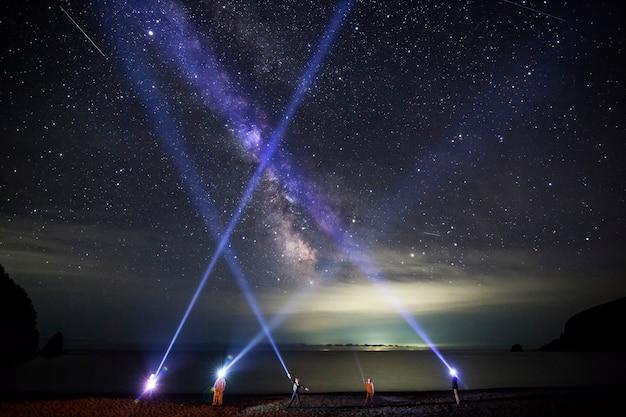 Le persone brillano con le torce a led alla notte furba con la via lattea