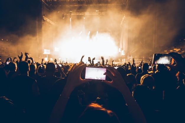 Sagome di persone al concerto di musica. folla e fan che mostrano amore per la rock band al festival