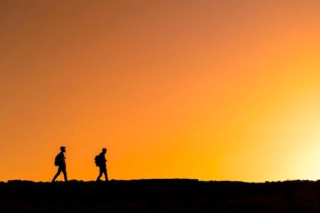 Sagome di persone che camminano sulla montagna al tramonto colorato. concetto di escursionismo